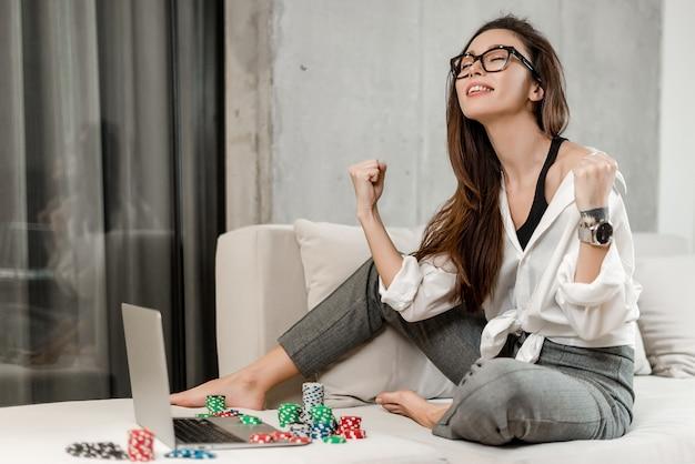 Mädchen, das online poker auf laptop spielt und geld im kasino gewinnt