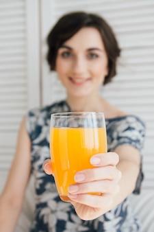 Mädchen, das orangensaft am frühstück im bett trinkt