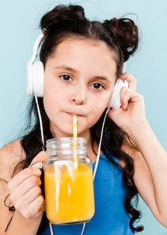 Mädchen, das orangensaft während hörende musik trinkt