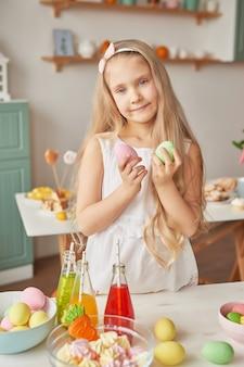 Mädchen, das ostereier an der küche hält