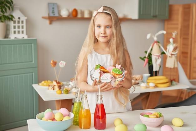 Mädchen, das osterplätzchen an der küche hält