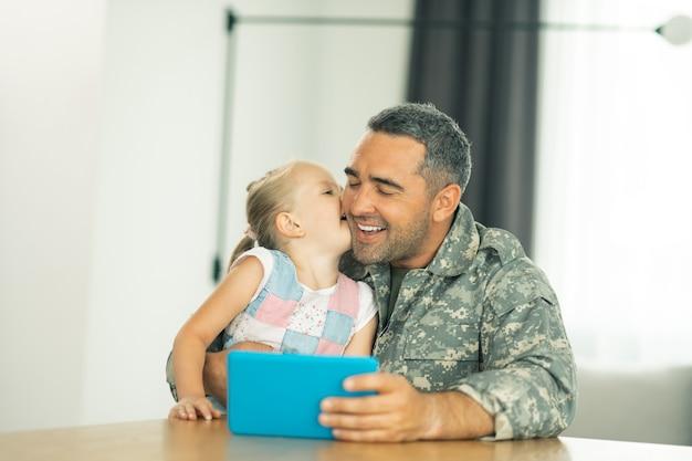 Mädchen, das papa küsst. schönes mädchen, das papa in militäruniform küsst, während es am tisch sitzt sitting