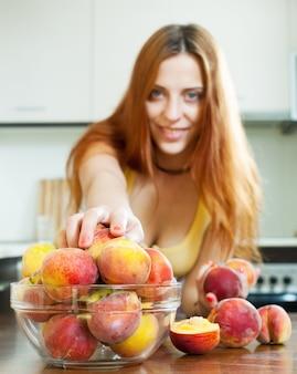 Mädchen, das pfirsiche zu hause küche nimmt
