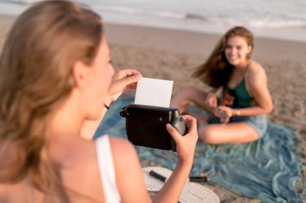 Mädchen, das polaroidbild von der sofortigen kamera am strand nimmt