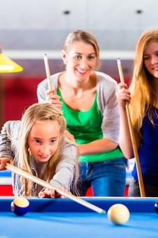 Mädchen, das poolbillard mit familie spielt