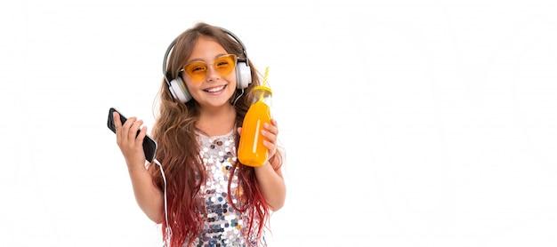 Mädchen, das prickelndes kleid und gelbe sonnenbrille, mit großen weißen kopfhörern trägt, musik hört und schwarzen smartphone und flasche mit orangensaft lokalisiert hält