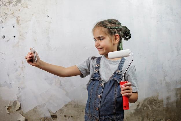 Mädchen, das raum repariert, die wand mit weißer farbe malt und selfie auf smartphone macht
