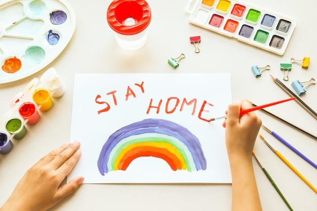 Mädchen, das regenbogen auf papier während der covid-19-quarantäne zu hause malt. zu hause bleiben