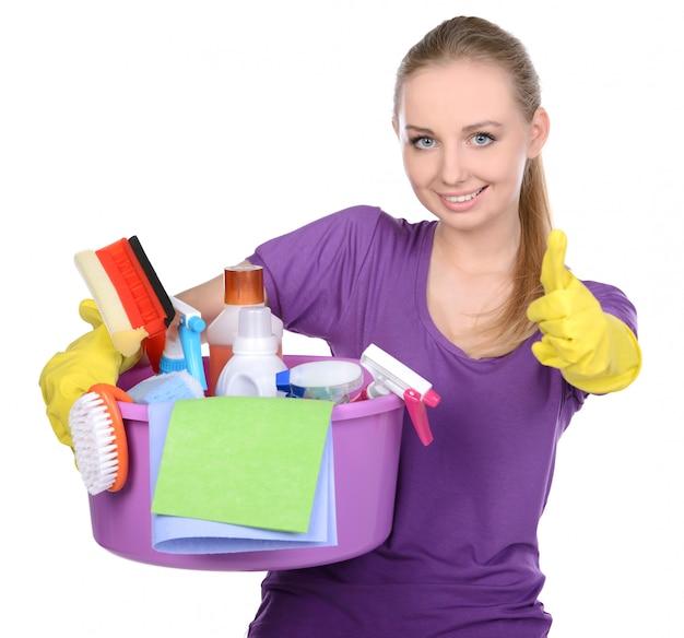 Mädchen, das reinigungsmittel hält und sich daumen zeigt.