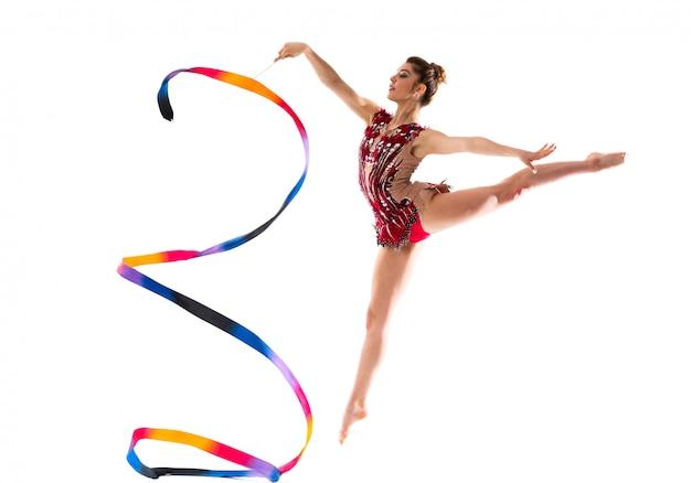 Mädchen, das rhythmische gymnastik mit dem farbbandspringen tut