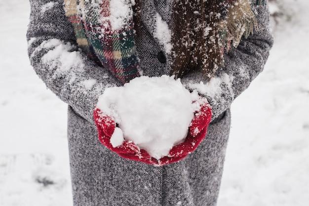 Mädchen, das rote bedeckte handschuhe trägt, die schnee halten