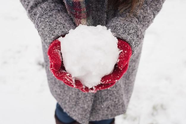 Mädchen, das rote bedeckte handschuhe trägt, die schnee mit frohen weihnachtsgruß halten