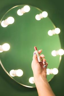 Mädchen, das roten lippenstift vor einem spiegel hält