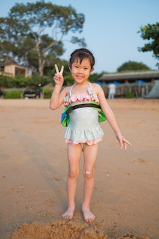 Mädchen, das sand am strand spielt, kinder, die im meer spielen