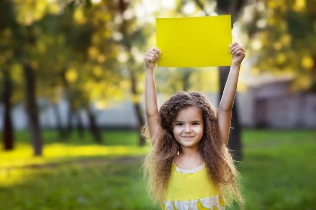 Mädchen, das sauberes weißes blattpapier hält. banner für ihre nachricht