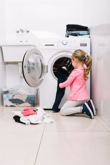 Mädchen, das schmutzige wäscherei in waschmaschine setzt