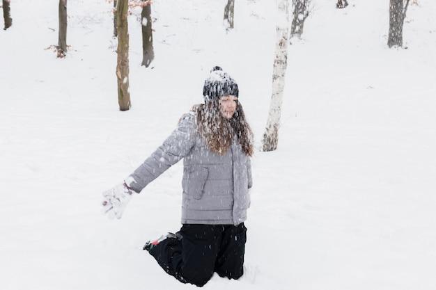 Mädchen, das schnee im park spielt