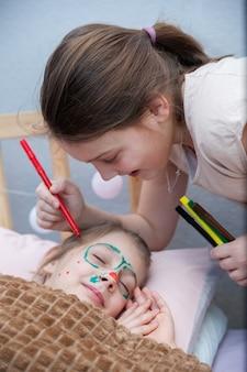 Mädchen, das schnurrbart auf gesicht ihrer schlafenden schwester zeichnet. erster april