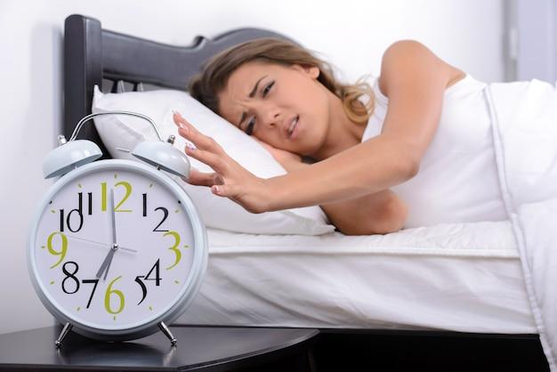 Mädchen, das sehr früh aufwachte, um einen wecker zu rufen.