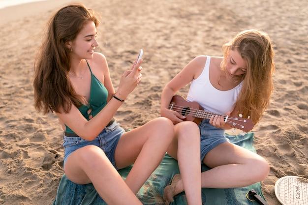 Mädchen, das selfie ihres freundes spielt ukulele am strand nimmt