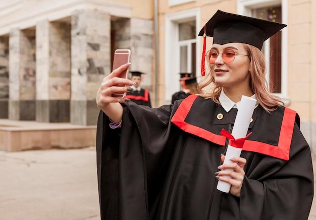 Mädchen, das selfie mit diplom nimmt
