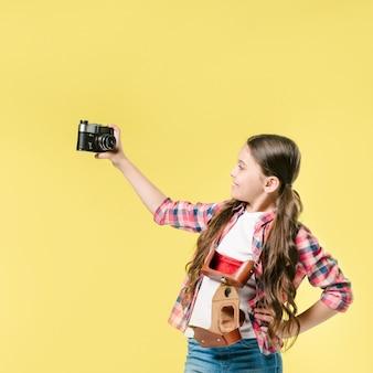 Mädchen, das selfie mit kamera im studio nimmt