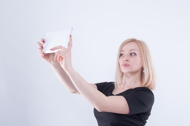 Mädchen, das selfie mit tablette macht. schließen sie oben vom jungen blonden schönen mädchen im schwarzen kleid, das in der weißen tablette in ihren händen schaut, die entengesicht machen