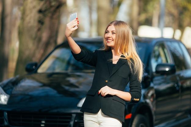 Mädchen, das selfie nahe neuem auto nimmt