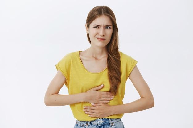 Mädchen, das sich krank fühlt, den bauch berührt und sich über krämpfe oder schmerzen beschwert