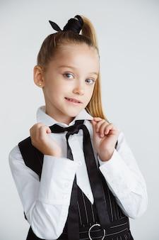 Mädchen, das sich nach einer langen sommerpause auf die schule vorbereitet. zurück zur schule. kleines weibliches kaukasisches modell, das in der schuluniform auf weißem studiohintergrund aufwirft. kindheit, bildung, ferienkonzept.