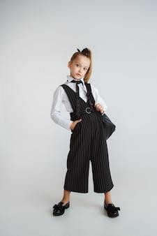 Mädchen, das sich nach einer langen sommerpause auf die schule vorbereitet. zurück zur schule. kleines weibliches kaukasisches modell, das in der schuluniform mit rucksack auf weißem hintergrund aufwirft. kindheit, bildung, ferienkonzept.