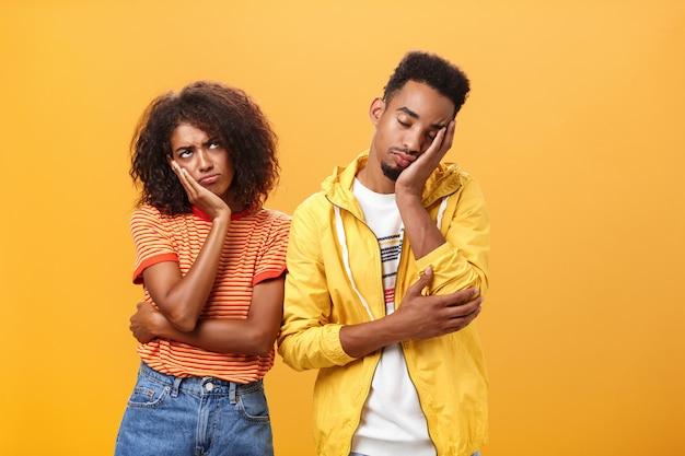 Mädchen, das sich unzufrieden und beleidigt über einen freund fühlt, der während des dates eingeschlafen ist und die lippen runzelt und die stirn runzelt, während der freund mit geschlossenen augen und müdeem blick über die orangefarbene wand den kopf auf das gesicht lehnt