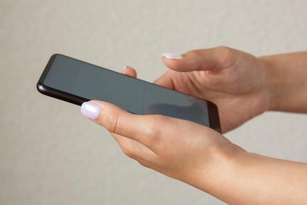 Mädchen, das smartphone in der handnahaufnahme hält