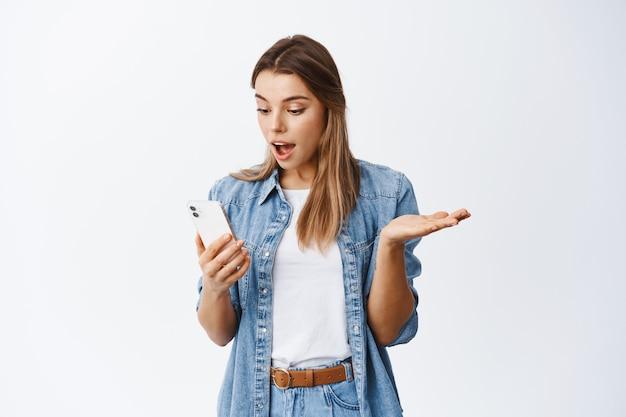 Mädchen, das smartphone überprüft, mit zufriedenem gesicht auf den bildschirm schaut, weiße wand