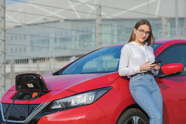 Mädchen, das smartphone und wartendes netzteil verwendet, verbinden sich mit elektrofahrzeugen zum laden der batterie im auto. ökologisches auto angeschlossen und batterien aufgeladen