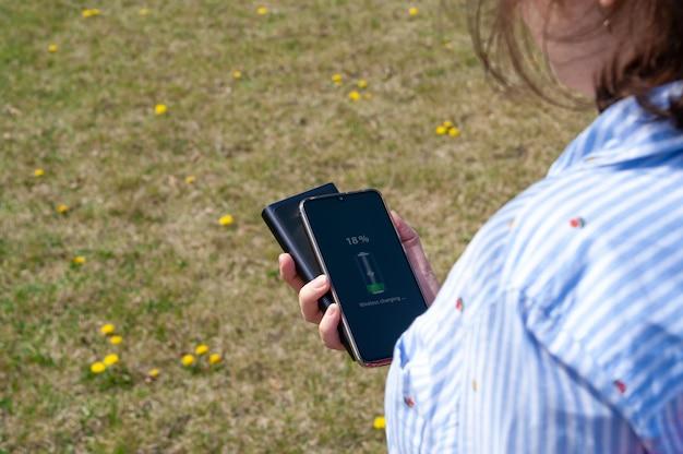 Mädchen, das smartphone von der induktionsenergiebank im park auflädt