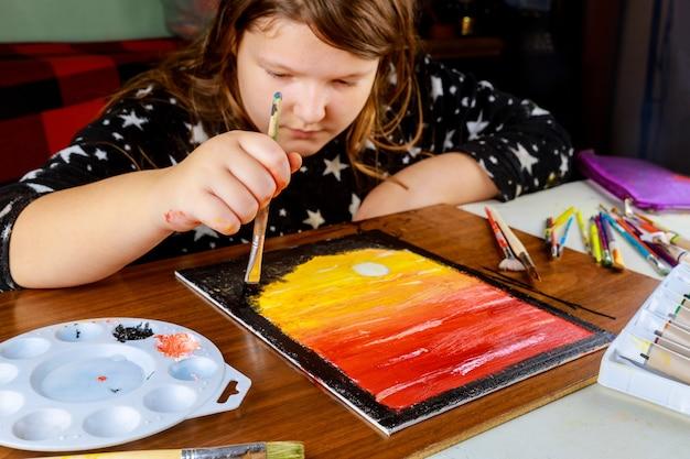 Mädchen, das sonnenuntergang mit ölfarbe auf leinwand malt. kunstwerk, kunst.