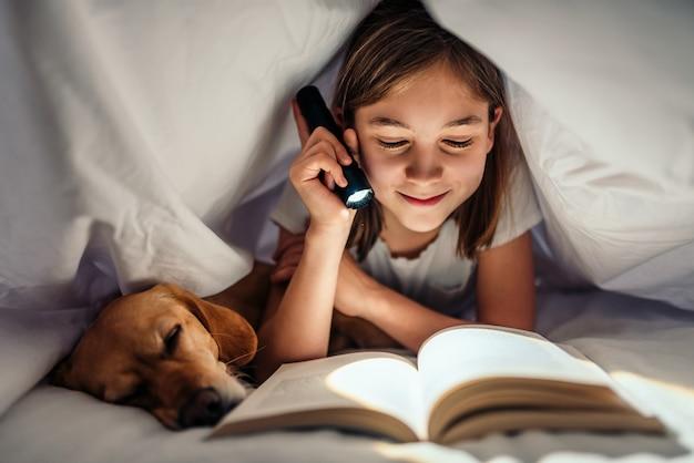 Mädchen, das spät im bett mit ihrem hund unter umfassendem lesebuch nachts liegt