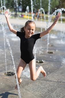 Mädchen, das spaß am wasserbrunnen hat
