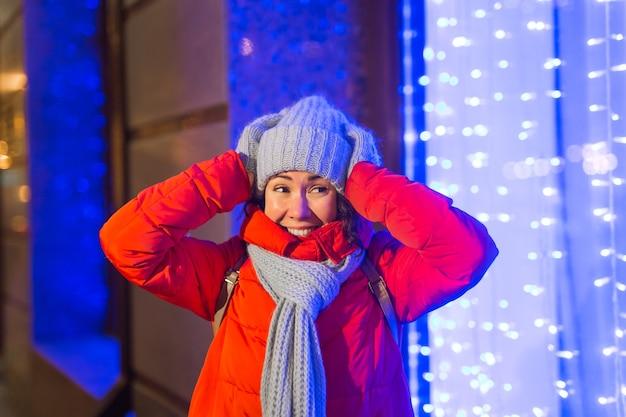 Mädchen, das spaß auf der weihnachtsdekoration hat, beleuchtet straße. junge glückliche lächelnde frau, die draußen stilvollen gestrickten schal und jacke trägt. modell lachen. winterwunderland-stadtszene, silvesterparty.