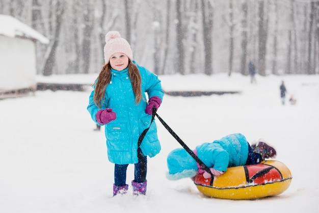 Mädchen, das spaß auf schneeröhre hat. mädchen reitet einen schlauch. winterferien, urlaub für kinder im winter. winterstadtpark.