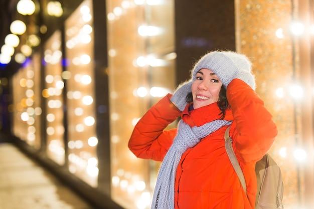 Mädchen, das spaß auf weihnachtsdekoration hat, beleuchtet straße junge glückliche lächelnde frau, die stilvolles trägt