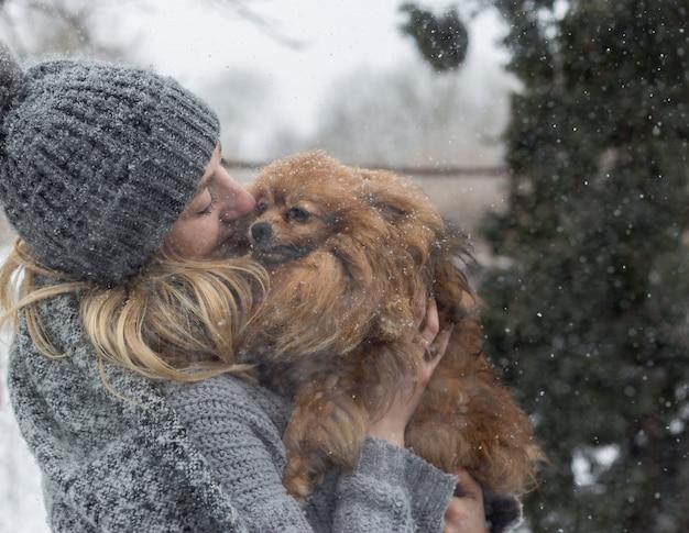 Mädchen, das spaß draußen im schnee mit ihrem hund yorkshire terrier hat.