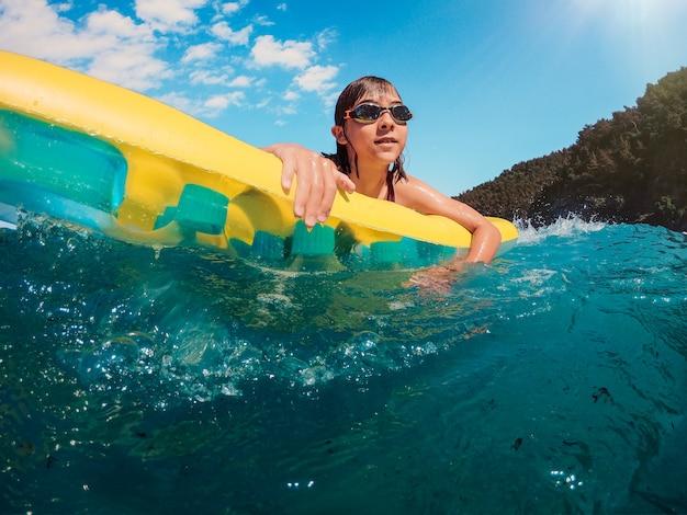 Mädchen, das spaß hat, auf die luftmatratze im meer zu schwimmen