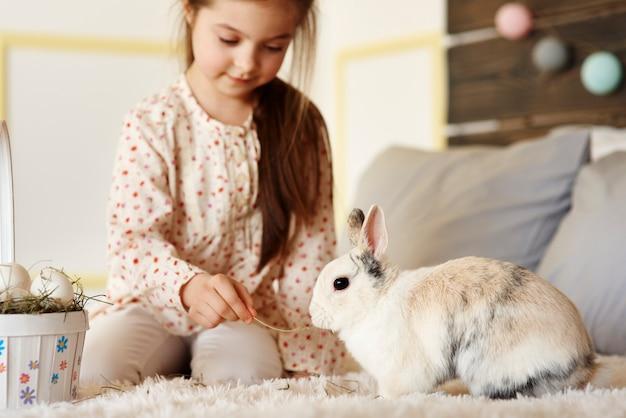 Mädchen, das spaß mit kaninchen auf dem bett hat