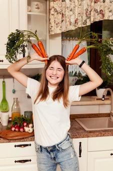 Mädchen, das spaß mit karotten in der küche hat