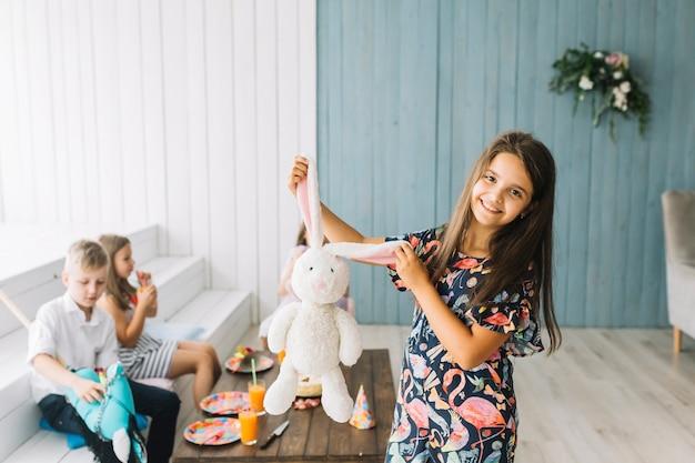 Mädchen, das spielzeughäschen auf geburtstagsfeier zeigt