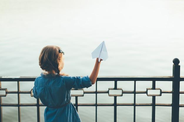 Mädchen, das spielzeugpapierflugzeug startet, das zum see schaut