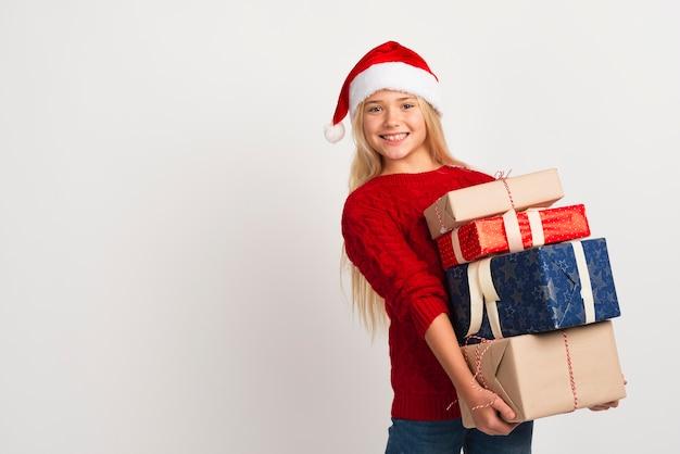Mädchen, das stapel von geschenken hält