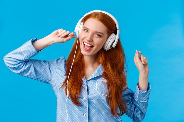 Mädchen, das starttag mit musik aufwacht. freudiger sorgloser rothaariger teenager, der in der nachtwäsche tanzt, die hände hebt und große weiße kopfhörer trägt, die entlang lieblingslied, wiedergabeliste, blauer hintergrund singen